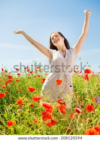 happiness, nature, summer, vacation and people concept - smiling young woman on poppy field
