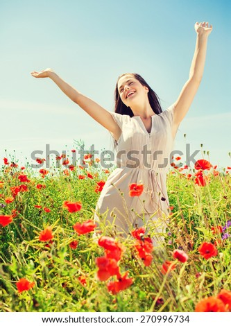happiness, nature, summer, vacation and people concept - smiling young woman on poppy field - stock photo