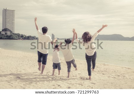 Happiness of Asian family on the beach on summer vacation with vintage color tone