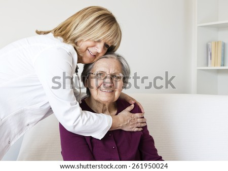 Happiness senior woman sitting on the sofa  at home  looking at camera and enjoying while the  mature nurse  embracing to her. - stock photo