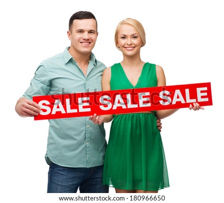 happiness, shopping and couple concept - smiling couple with sale sing - stock photo