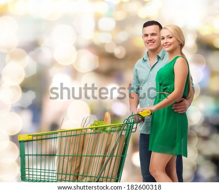 happiness, shopping and couple concept - smiling couple with shopping cart and food in it - stock photo