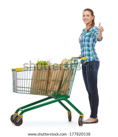 happiness, shopping and people concept - smiling young woman with shopping cart and food in it showing thumbs up