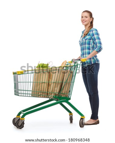 happiness, shopping and people concept - smiling young woman with shopping cart and food in it