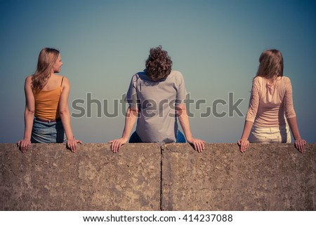 Happiness summer friendship concept. Group of friends spending time together having fun outdoor sitting on wall against blue sky - stock photo