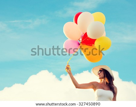 happiness, summer, holidays and people concept - smiling young woman wearing sunglasses with balloons over blue sky and cloud background - stock photo