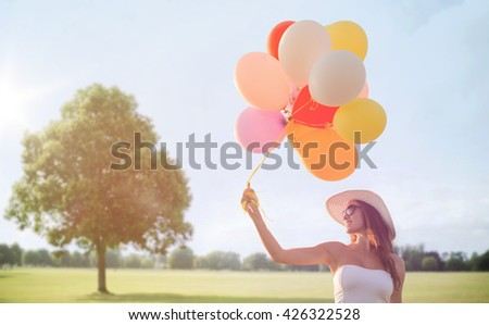 happiness, summer, holidays and people concept - smiling young woman wearing sunglasses with balloons over summer park background - stock photo