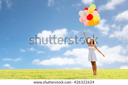 happiness, summer, holidays and people concept - smiling young woman wearing sunglasses with balloons over blue sky and grass background - stock photo