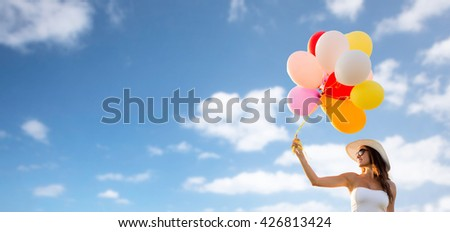 happiness, summer, holidays and people concept - smiling young woman wearing sunglasses with balloons over blue sky background - stock photo