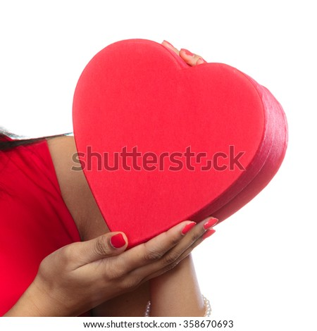 Happiness, valentines day and love concept. elegant woman in red dress, girl mixed race holding red heart-shaped gift box in hands on white