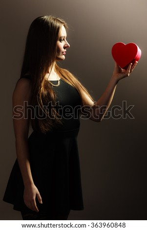 Happiness, valentines day and love concept. Lovely elegant pensive woman in black dress holding red heart-shaped gift box on gray - stock photo