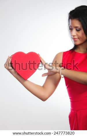 Happiness, valentines day and love concept. Lovely elegant woman in red dress, girl mixed race holding red heart-shaped gift box on gray - stock photo