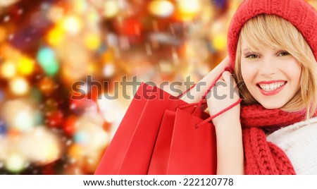 happiness, winter holidays, christmas and people concept - smiling young woman in hat and scarf with shopping bags over red lights background