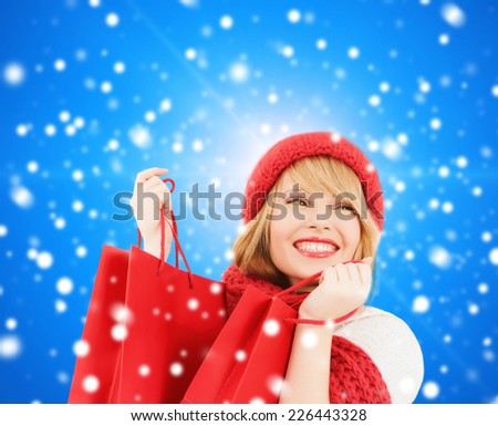 happiness, winter holidays, christmas and people concept - smiling young woman in hat and scarf with shopping bags over blue snowy background - stock photo