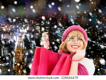 happiness, winter holidays, christmas and people concept - smiling young woman in hat and scarf with pink shopping bags ove snowy night city background - stock photo