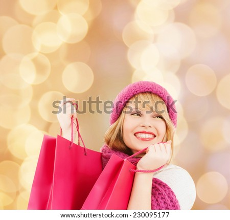 happiness, winter holidays, christmas and people concept - smiling young woman in hat and scarf with pink shopping bags over beige lights background