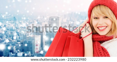 happiness, winter holidays, christmas and people concept - smiling young woman in hat and scarf with shopping bags over snowy city background - stock photo