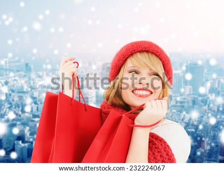 happiness, winter holidays, christmas and people concept - smiling young woman in hat and scarf with shopping bags over snowy city background
