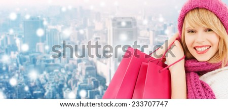 happiness, winter holidays, christmas and people concept - smiling young woman in hat and scarf with pink shopping bags ove snowy city background