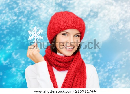 happiness, winter holidays, christmas and people concept - smiling young woman in red hat, scarf and mittens holding snowflake over blue lights background
