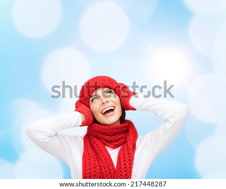 happiness, winter holidays, christmas and people concept - smiling young woman in red hat, scarf and mittens over blue lights background