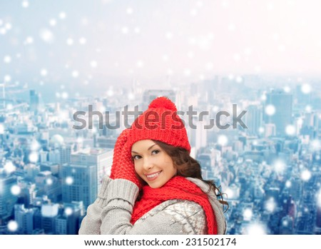 happiness, winter holidays, christmas and people concept - smiling young woman in red hat, scarf and mittens over snowy city background