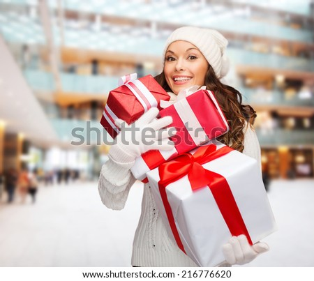 happiness, winter holidays, christmas and people concept - smiling young woman in santa helper hat with gifts over shopping center background - stock photo