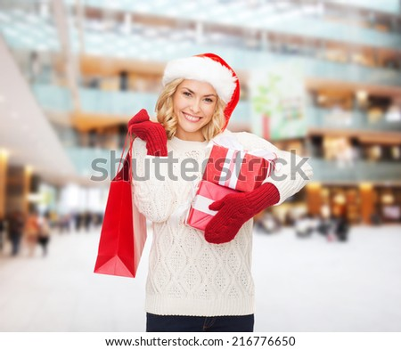 happiness, winter holidays, christmas and people concept - smiling young woman in santa helper hat with gifts and shopping bag over mall background - stock photo