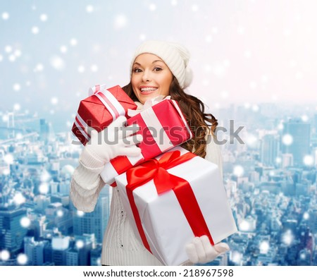 happiness, winter holidays, christmas and people concept - smiling young woman in santa helper hat with gifts over snowy city background