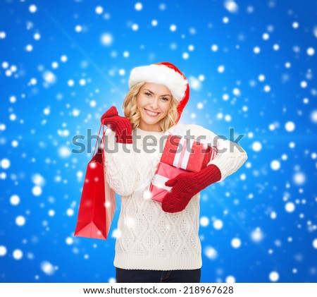 happiness, winter holidays, christmas and people concept - smiling young woman in santa helper hat with gifts and shopping bag over blue snowing background - stock photo