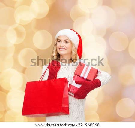 happiness, winter holidays, christmas and people concept - smiling young woman in santa helper hat with gift boxes and shopping bag over beige lights background - stock photo