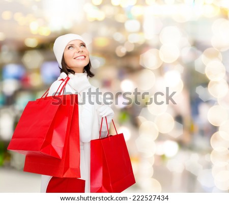 happiness, winter holidays, christmas and people concept - smiling young woman in white hat and mittens with red shopping bags over lights background - stock photo