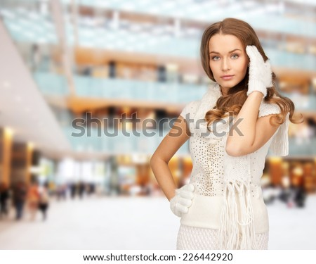happiness, winter holidays, christmas and people concept - smiling young woman in white warm clothes over shopping center background - stock photo