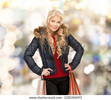 happiness, winter holidays, christmas and people concept - smiling young woman in winter clothes with shopping bags over lights background