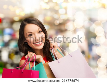 happiness, winter holidays, christmas and people concept - smiling young woman with shopping bags over lights background - stock photo