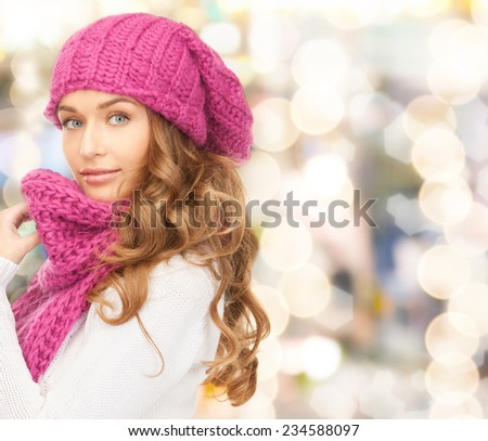 happiness, winter holidays, christmas and people concept - young woman in pink hat and scarf over lights background