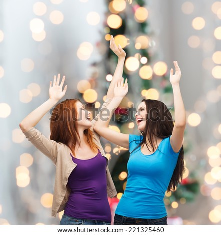 happiness, winter holidays, friendship and people concept - smiling teenage girls having fun over christmas tree background - stock photo