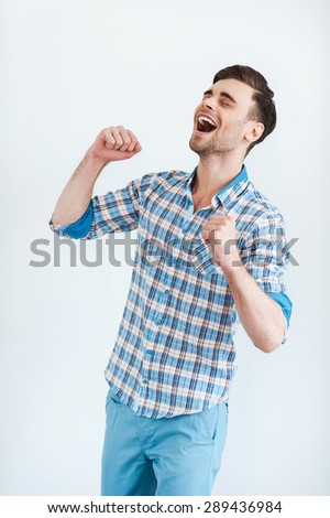 Happiness without limits. Cheerful young man in shirt gesturing and smiling while standing against white background - stock photo