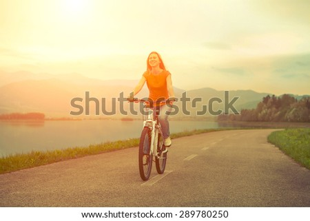 Happiness woman on the bicycle outdoor. - stock photo