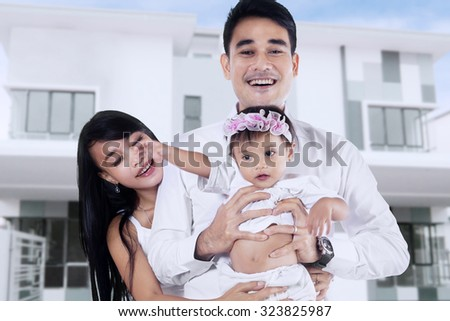 Happiness young asian family standing in front of new home