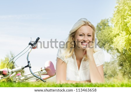 Happiness young blond woman relaxing on green grass after cycling.Bicycle in the background.