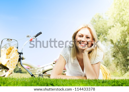 Happiness young blond woman relaxing on green grass after cycling.Bicycle in the background. - stock photo