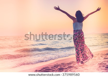 Happiness Young woman on the beach at sunset times - vintage effect and light leak filter processing style pictures - stock photo