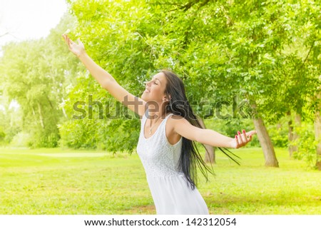 Happiness young woman with sprading hands enjoyment in the nature and beautiful day. - stock photo