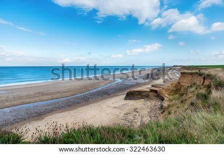Happisburgh beach and eroding cliffs on the Norfolk coast - stock photo