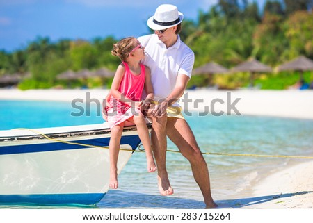 Happpy father and daughter on boat during tropical beach vacation - stock photo