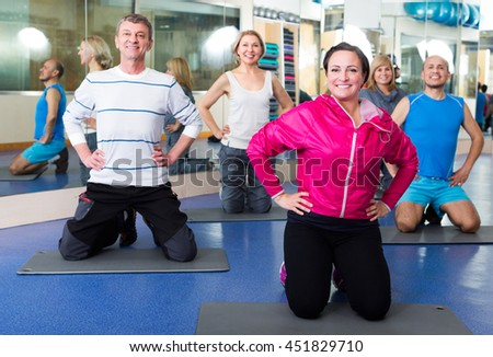 Happy active adults doing pilates routine in a sport club - stock photo