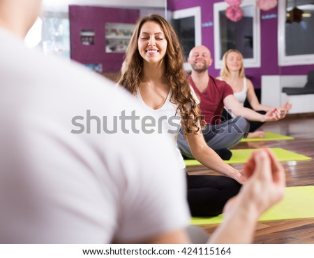 Happy active adults having yoga class in sport club - stock photo