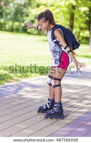 Happy Active and Sportive African American Female Teenager Having Fun on Roller Skates in Park. Vertical Image