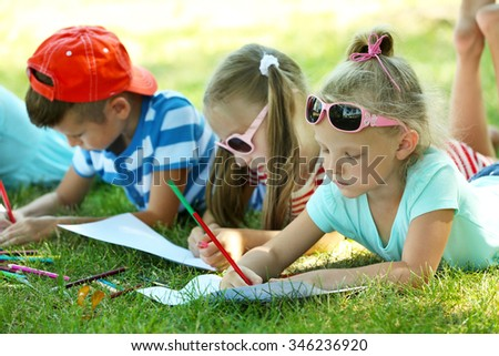 Happy active children lying on green grass and drawing in park